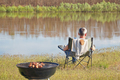 Man is sitting on a shore of river and making barbecue - PhotoDune Item for Sale
