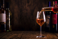 Wine tasting. Rose wine pouring into glass on wooden background - PhotoDune Item for Sale
