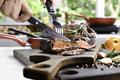 Slicing grilled beef steaks - PhotoDune Item for Sale