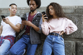 Bottom view of three young people standing with mobile phones - PhotoDune Item for Sale
