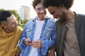Three young men laughing at something holding mobile phone - PhotoDune Item for Sale