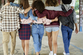 Rear view of stylish friends walking on urban street - PhotoDune Item for Sale