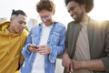 Three young men standing and scrolling a cell phone - PhotoDune Item for Sale