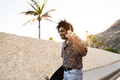 African american man holding longboard on the road with palm trees in the background - Focus on face - PhotoDune Item for Sale