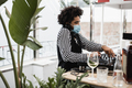 African dj playing music at cocktail bar outdoor while wearing face safety mask - Focus on face - PhotoDune Item for Sale
