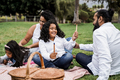 Indian parents having fun painting with children outdoor at city park - Main focus on boy face - PhotoDune Item for Sale