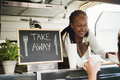 African woman serving takeaway food with eco paper boxes inside food truck - Focus on face - PhotoDune Item for Sale