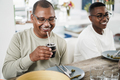 Happy black father drinking yerba mate during lunch at home - Main focus on man face - PhotoDune Item for Sale