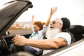 Happy senior couple having fun in convertible car during summer vacation - Focus on man face - PhotoDune Item for Sale