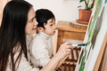 Asian kid and mom painting on canvas during art class at home - Focus on woman eye - PhotoDune Item for Sale