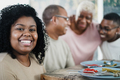 Happy black young woman eating lunch with her family at home - Focus on girl face - PhotoDune Item for Sale