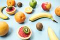 Colorful fresh fruit on Gray table. Orange, banana, apples, kiwi, grapefruit. Flat lay, - PhotoDune Item for Sale