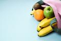 Variety of  fruits grapefruit, kiwi, banana, orange from pink linen bag over blue background. - PhotoDune Item for Sale