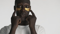 Young African American man applying eye patches over white background. Facial treatment - PhotoDune Item for Sale