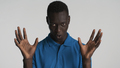 Young African American man showing wow gesture looking sly on camera over white background - PhotoDune Item for Sale