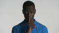 Young African American man showing silence gesture looking serious on camera over white background - PhotoDune Item for Sale