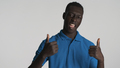 Handsome cool African American guy keeping thumbs up rejoicing on camera over white background - PhotoDune Item for Sale