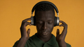 Young African American man in headphones moving on music isolated on colorful background - PhotoDune Item for Sale