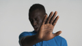 Young afraid African American man closing eyes from fear covering camera with hand isolated - PhotoDune Item for Sale