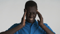 Portrait of depressed African American man showing headache on camera over white background - PhotoDune Item for Sale