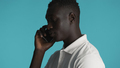 Side view of attractive African American guy talking on smartphone isolated on blue background - PhotoDune Item for Sale