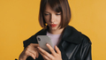 Beautiful girl with bob hair using smartphone on camera isolated on yellow background - PhotoDune Item for Sale