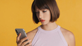 Serious girl with bob hair getting message from boyfriend feeling sad isolated on yellow background - PhotoDune Item for Sale