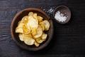 Homemade crispy Potato chips and sea salt on dark wooden background - PhotoDune Item for Sale