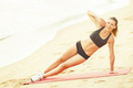 Beautiful woman is doing exercises on the shore - PhotoDune Item for Sale