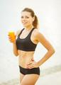 Beautiful woman in sportswear drinking juice on the beach. - PhotoDune Item for Sale