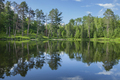 Calm blue lake and trees on a sunny evening in northern Minnesota during summer - PhotoDune Item for Sale