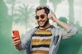 Young hipster man listening music on mobile phone while wearing headphones outdoor - Focus on face - PhotoDune Item for Sale