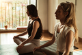 Young people doing yoga class indoor at fitness studio - Focus on right girl face - PhotoDune Item for Sale
