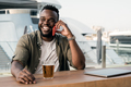 African man drinking beer at brewery bar using mobile phone with luxury yacht port in background - PhotoDune Item for Sale