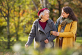 Senior woman walking with granddaughter in park during autumn - PhotoDune Item for Sale
