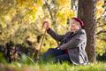 Senior woman relaxing at park during autumn season - PhotoDune Item for Sale