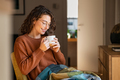 Relaxed young woman drinking hot tea at home - PhotoDune Item for Sale