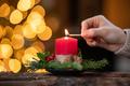 Woman lighting christmas advent candle - PhotoDune Item for Sale