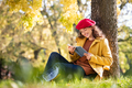 Young woman reading book in park during autumn season - PhotoDune Item for Sale
