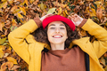 Smiling woman lying on autumn leaves - PhotoDune Item for Sale