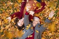 Grandmother and granddaughter lying on foliage and enjoy the autumn - PhotoDune Item for Sale