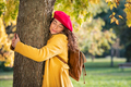 Young woman hugging tree in atumn at park - PhotoDune Item for Sale