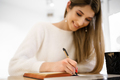 Smiling woman in white sweater writing in notebook - PhotoDune Item for Sale