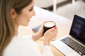 Young female at cafe using laptop and drinking latte - PhotoDune Item for Sale