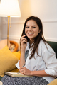 Cheerful Young Beautiful Woman Talking on the Phone Sitting on Couch - PhotoDune Item for Sale