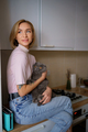 Woman siting on kitchen hugging a cat - PhotoDune Item for Sale