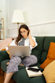 Businesswoman working on laptop computer sitting at home and managing her business via home office - PhotoDune Item for Sale