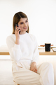 Smiling woman talking on the smartphone drinking coffee indoors - PhotoDune Item for Sale
