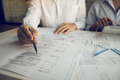 Architects engineer working with blueprints on table and discussing project together - PhotoDune Item for Sale