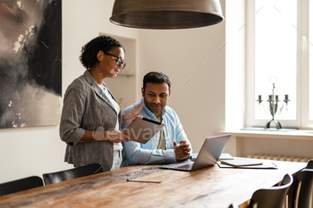 Middle eastern man and woman using laptop while working together